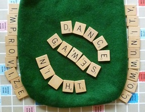 Photo of Scrabble game letters spelling: Dance Games Night. Improvize. Community.